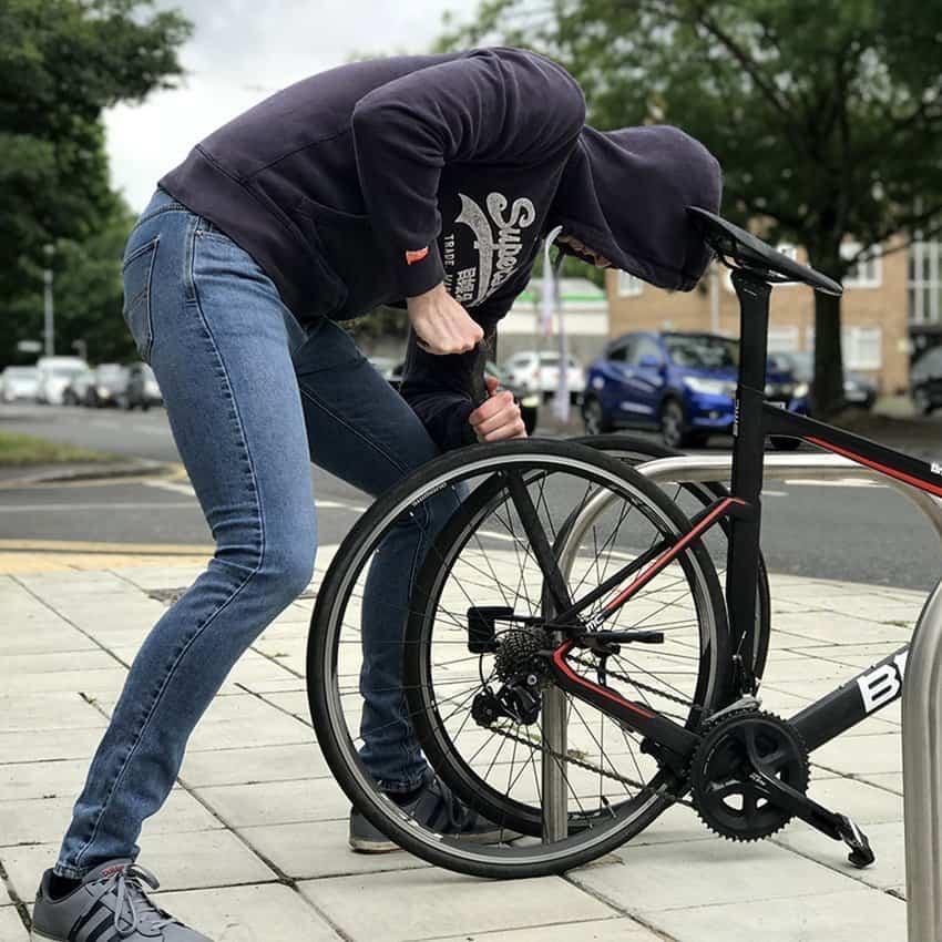 Thief stealing bike with crowbar