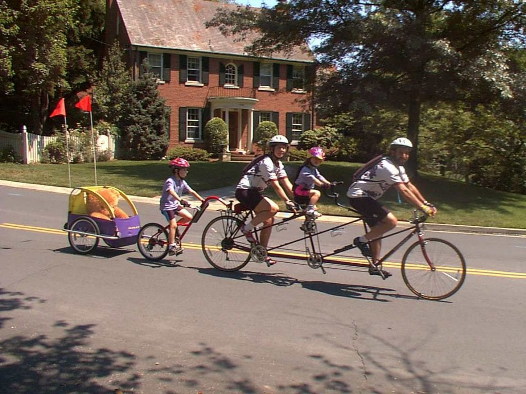 Family riding a tandem bike with children