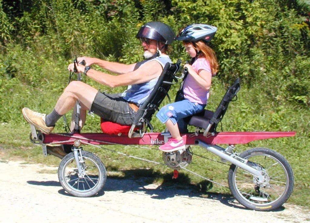 Grandfather and grand daughter riding recumbent tandem