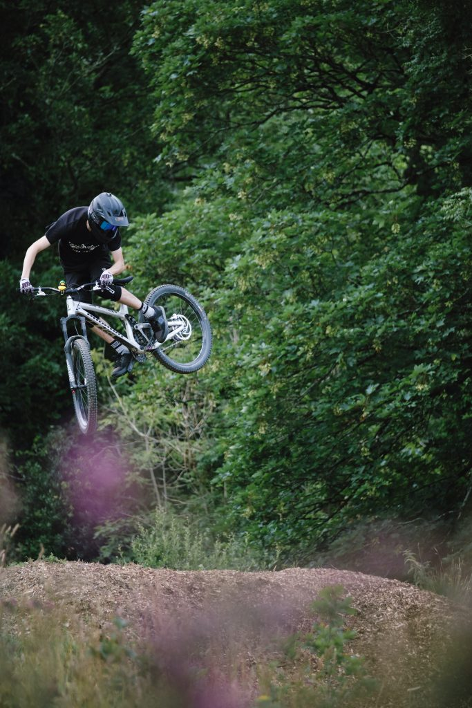 """27.5"""" mtb rider jumping over a ramp"""