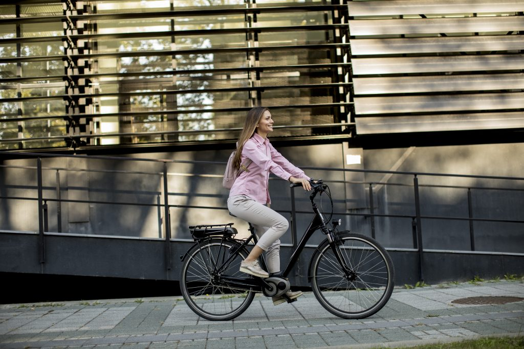 young woman riding electric city bike