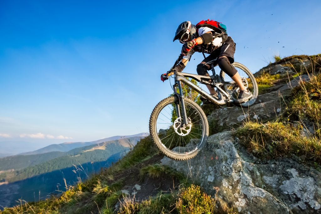 man riding enduro bike on mountain trail